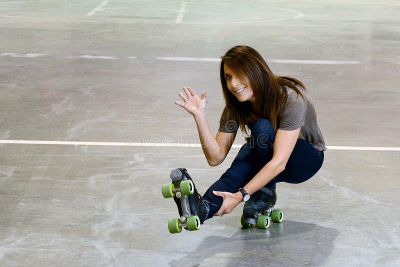 Mulher que faz o tiro o movimento do pato em patins de rolo do quadrilátero foto de stock