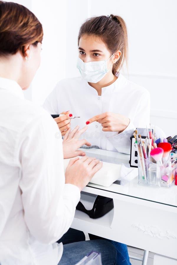 Mulher que faz o tratamento de mãos na técnica da goma-laca fotos de stock