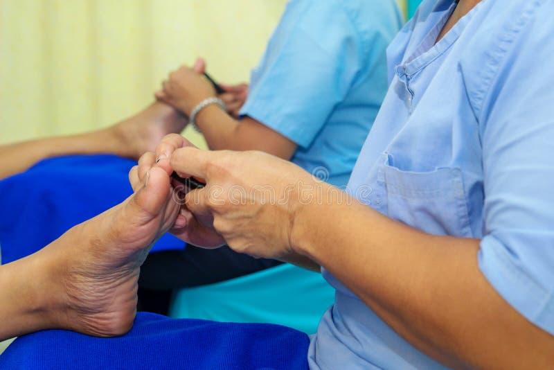 Mulher que faz o tratamento dos cuidados médicos da massagem do pé nos termas foto de stock