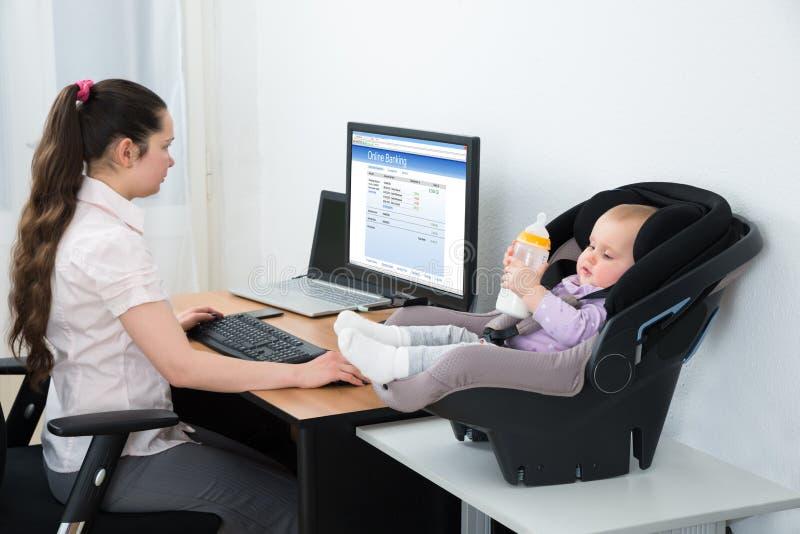 Mulher que faz a operação bancária em linha no computador imagem de stock