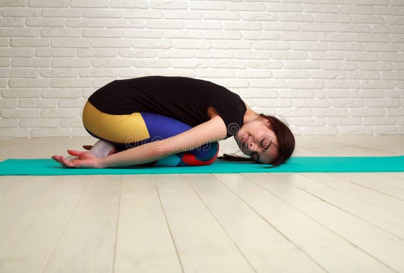 Mulher que faz os exercícios da ioga e da aptidão que esticam seu corpo foto de stock royalty free