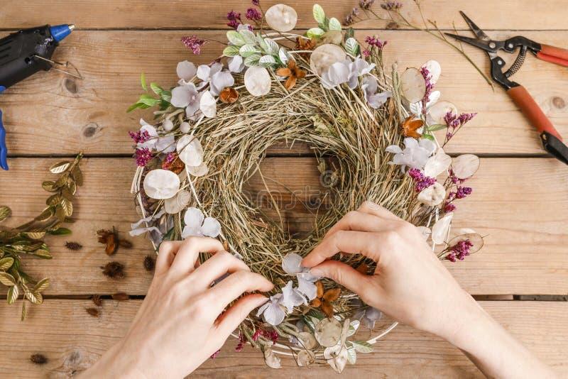 Mulher que faz a porta envolver-se com plantas e flores do outono imagem de stock royalty free