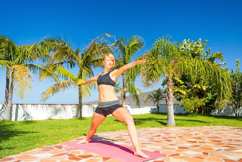 Mulher que faz a pose bonita do guerreiro da ioga imagens de stock royalty free