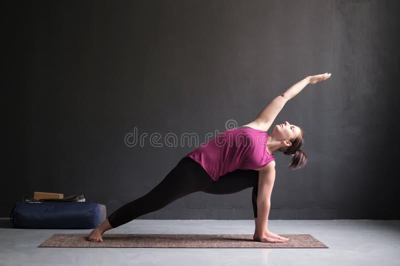 Mulher que faz postura prolongada do ângulo lateral, Utthita Parsva Konasana fotografia de stock royalty free