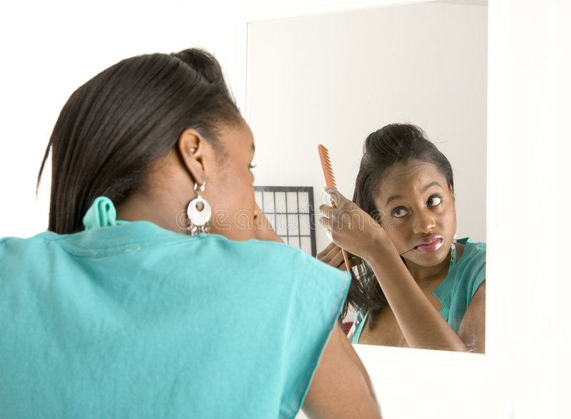 Mulher que faz seu cabelo no espelho fotografia de stock royalty free
