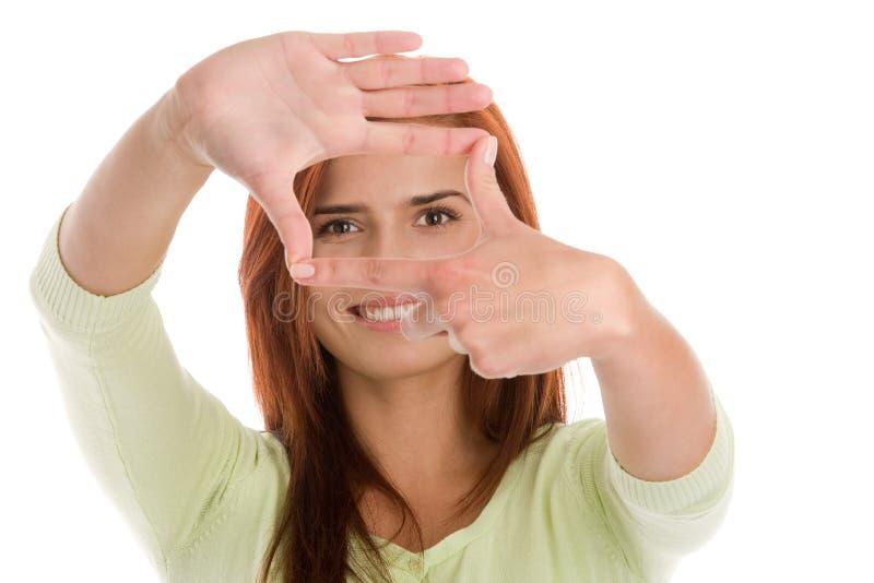 Mulher que faz um quadro com suas mãos fotografia de stock royalty free