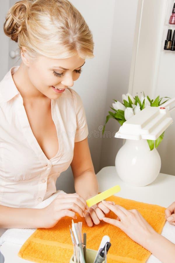 Mulher que faz um tratamento de mãos no salão de beleza foto de stock royalty free