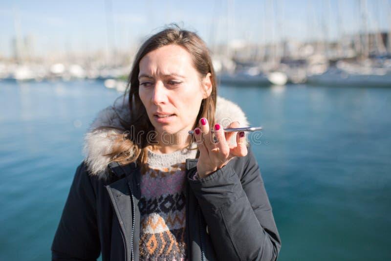 Mulher que faz uma massagem da voz no telefone fotografia de stock royalty free