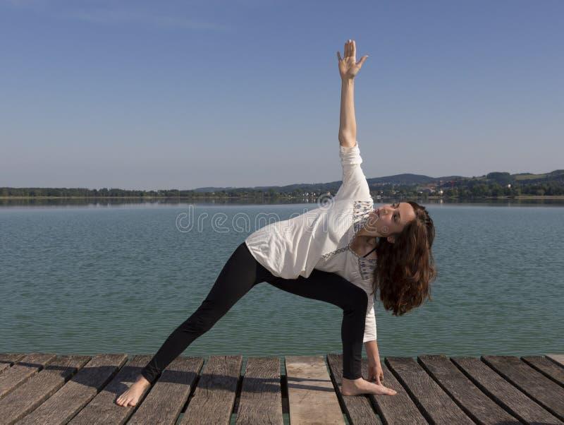 Mulher que faz uma variação de pose prolongada do ângulo lateral durante a ioga fotos de stock