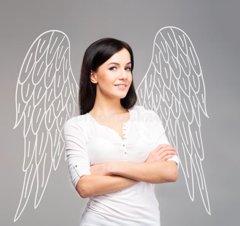 Mulher que finge ser um anjo sobre o fundo cinzento imagem de stock royalty free
