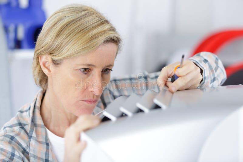 Mulher que fixa um dispositivo imagens de stock royalty free