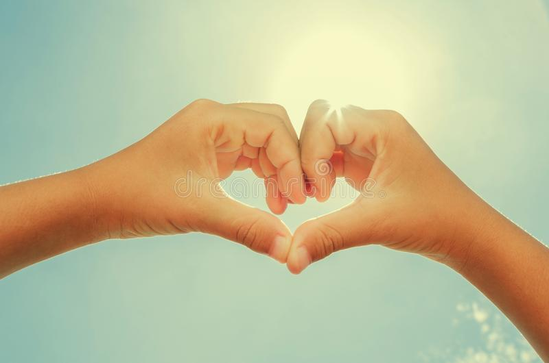 a mulher que forma o coração deu forma às mãos com instagram do sol do meio-dia fotografia de stock