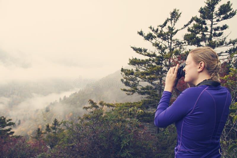 Mulher que fotografa montanhas quando em uma caminhada fotografia de stock royalty free