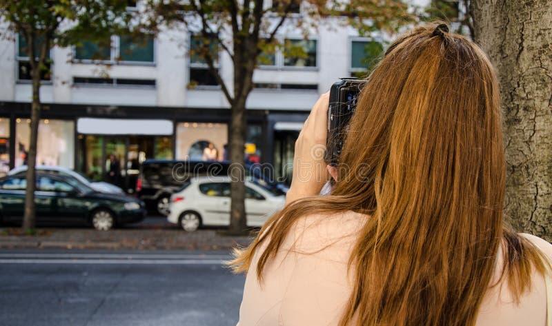 Mulher que fotografa na rua fotografia de stock