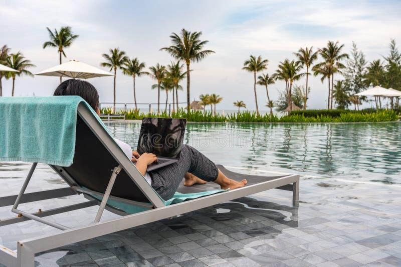 Mulher que freelancing no portátil nas férias na piscina bonita fotografia de stock royalty free