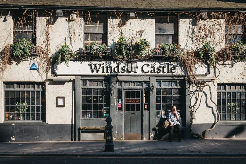 Mulher que fuma fora do bar de Windsor Castle em Holland Park, Londres, Reino Unido foto de stock