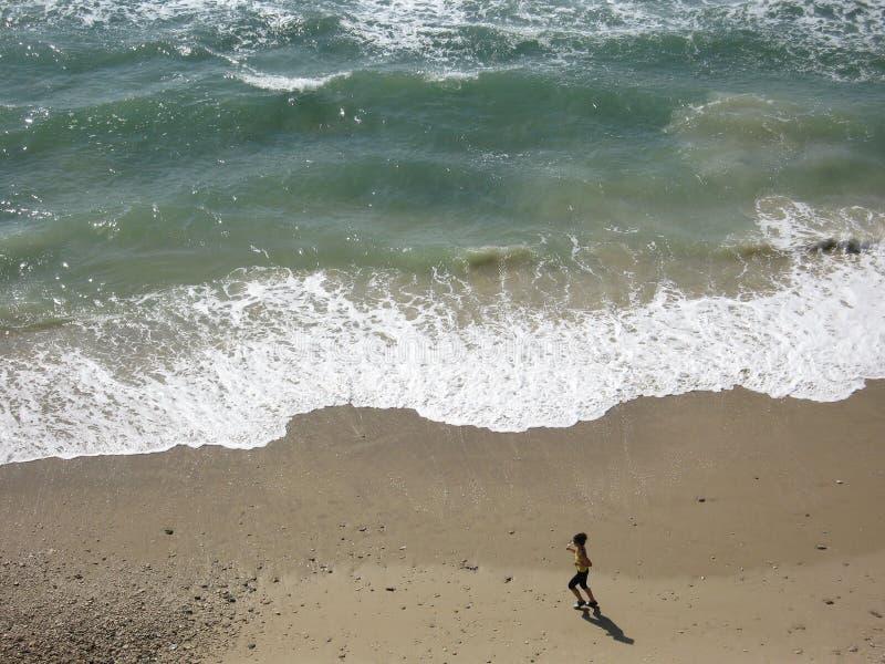 Mulher que funciona em uma praia fotografia de stock
