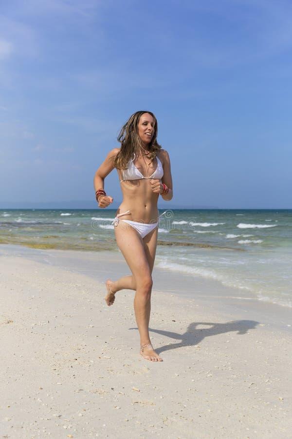 Mulher que funciona em uma praia foto de stock