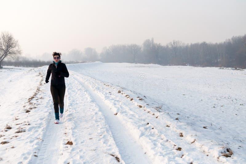 Mulher que funciona na neve imagens de stock royalty free