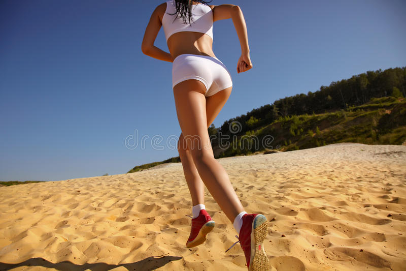 Mulher que funciona na praia fotos de stock