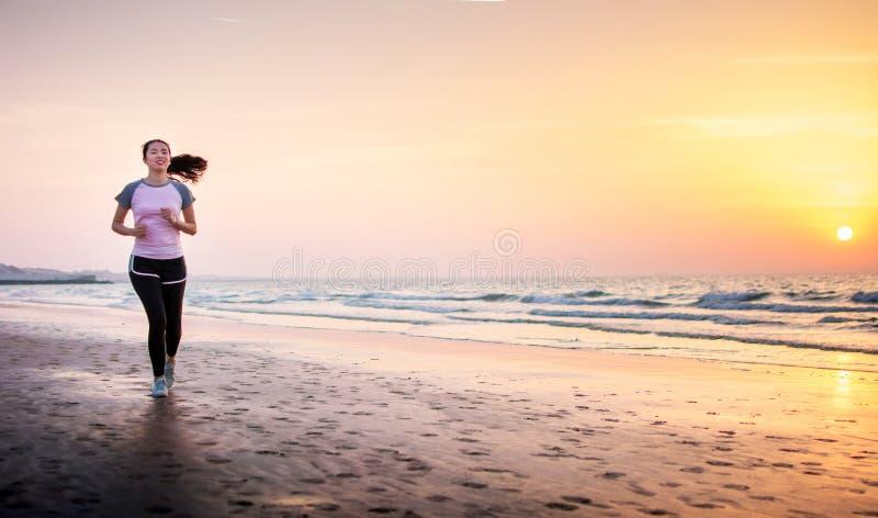 Mulher que funciona na praia no por do sol imagens de stock royalty free