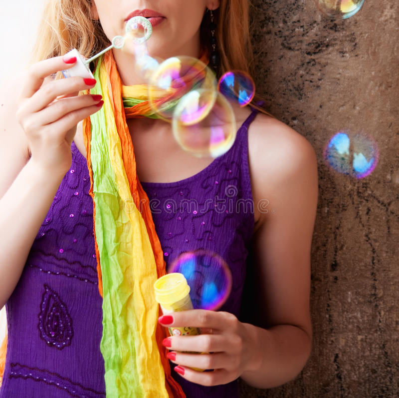 Mulher que funde bolhas de sabão coloridas fotos de stock royalty free
