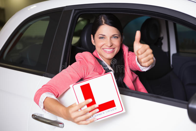 Mulher que gesticula os polegares que mantêm um sinal do motorista do principiantes fotografia de stock royalty free