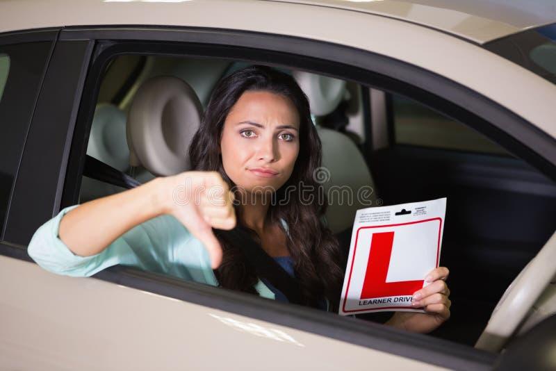 Mulher que gesticula os polegares que mantêm um sinal do motorista do principiantes foto de stock royalty free