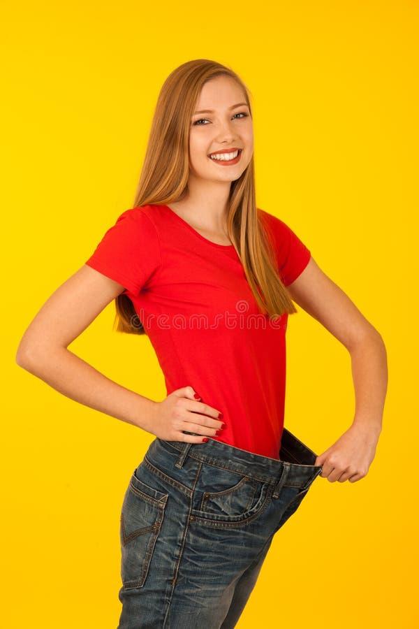 Mulher que gesticula a perda de peso que veste calças demasiado grandes fotografia de stock