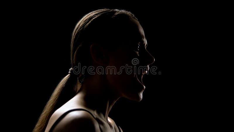 Mulher que grita contra o fundo preto, aliviando o esforço, psicoterapia foto de stock royalty free