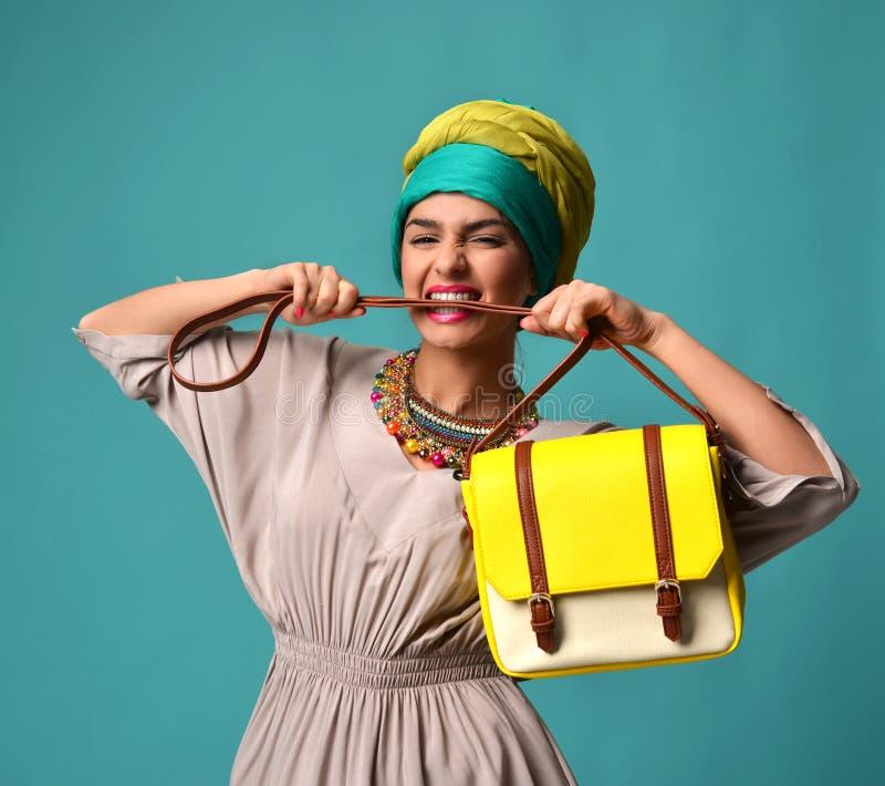 Mulher que grita gritar e comer a correia do handba à moda do saco de couro do amarelo da forma da posse da mão imagens de stock royalty free