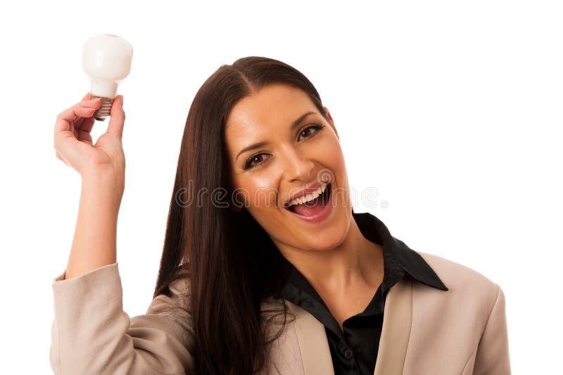 Mulher que guarda a ampola acima da cabeça como um sinal da ideia nova fotografia de stock