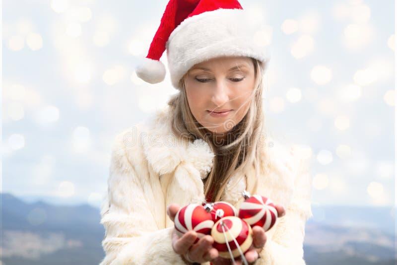 Mulher que guarda as quinquilharias do Natal - Natal em montanhas azuis foto de stock