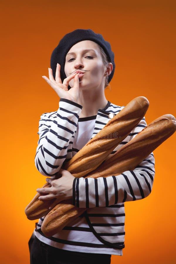 A mulher que guarda baguettes e mostra que o gosto é delicioso fotografia de stock royalty free