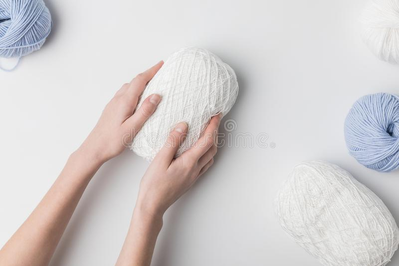Mulher que guarda a bola branca do fio nas mãos no fundo branco fotografia de stock