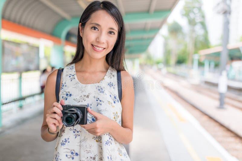 Mulher que guarda a câmara digital na estação de trilho clara fotografia de stock