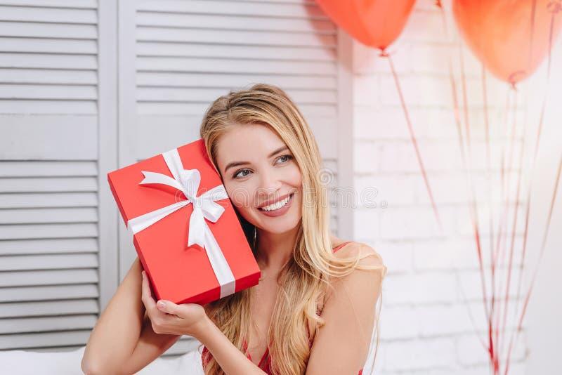 Mulher que guarda a caixa de presente vermelha na cara imagem de stock royalty free