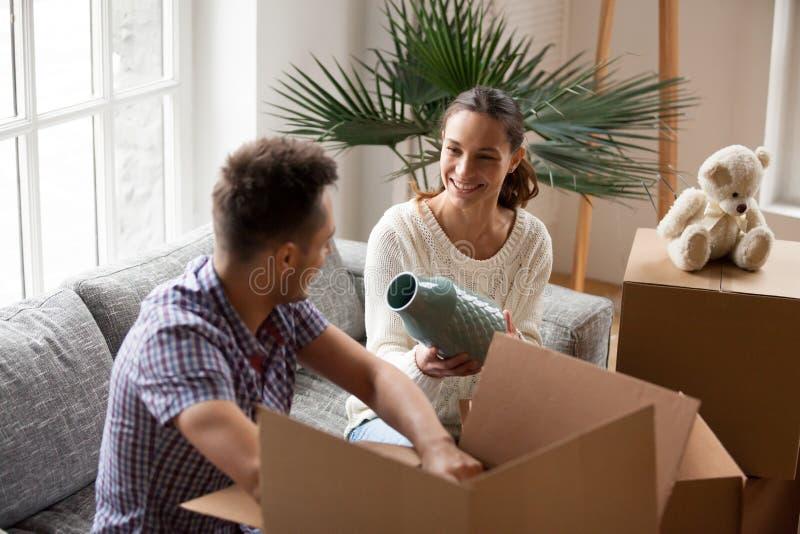 Mulher que guarda caixas de embalagem de ajuda do homem do vaso em dia movente fotografia de stock royalty free