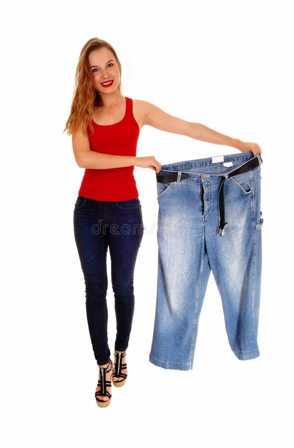 Mulher que guarda calças grandes fotos de stock royalty free