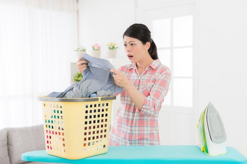 Mulher que guarda a camisa cinzenta que olha a área suja foto de stock