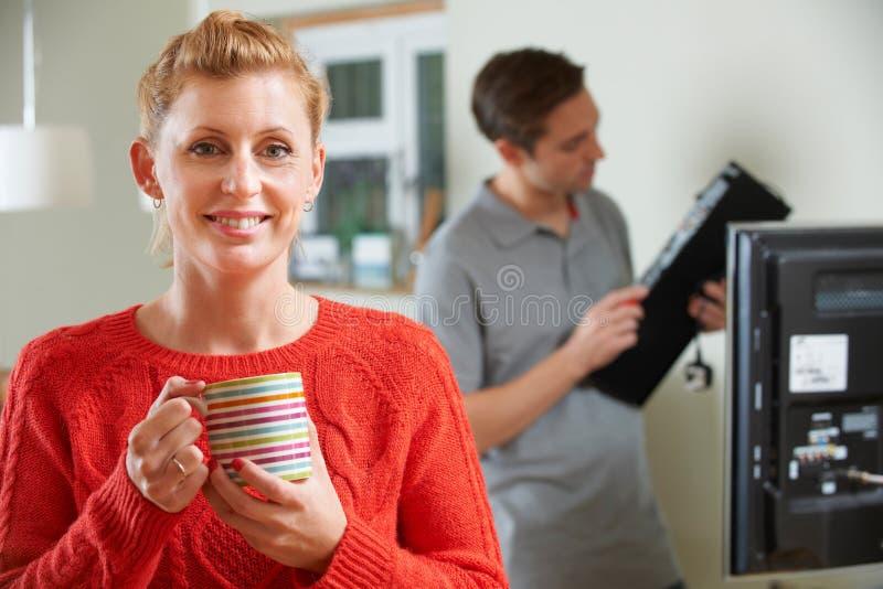 Mulher que guarda a caneca enquanto equipamento da tevê de Installs do coordenador foto de stock royalty free