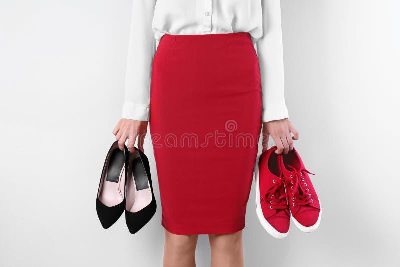 A mulher que guarda a elevação colocou saltos sapatas e sapatilhas no fundo branco, close up imagens de stock royalty free