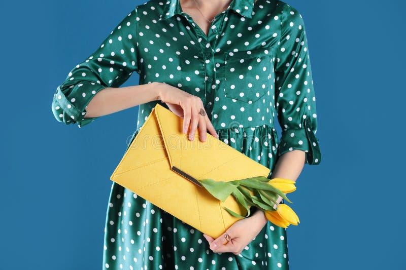 Mulher que guarda a embreagem elegante com as flores da mola no fundo azul fotografia de stock