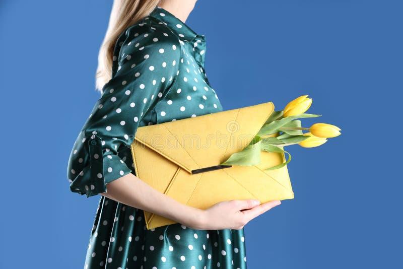 Mulher que guarda a embreagem elegante com as flores da mola no fundo azul fotos de stock