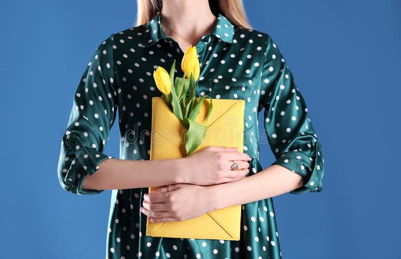 Mulher que guarda a embreagem elegante com as flores da mola no fundo azul fotos de stock royalty free