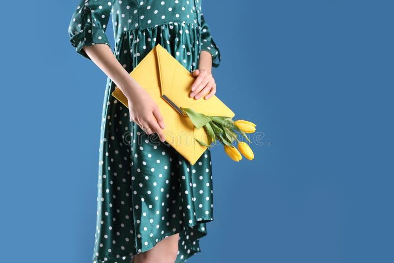 Mulher que guarda a embreagem elegante com as flores da mola no fundo azul, close up fotos de stock royalty free