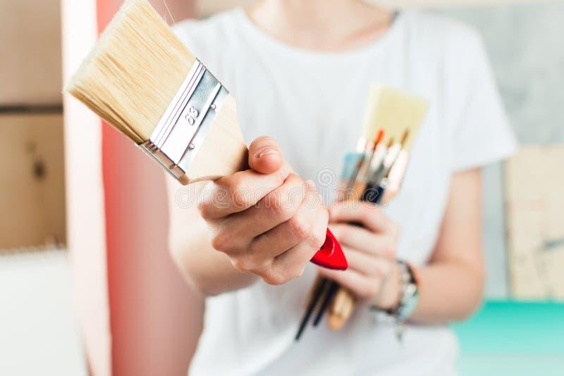 Mulher que guarda a escova de pintura em sua mão imagem de stock