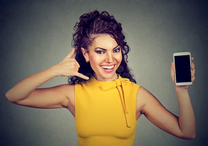 A mulher que guarda a exibição do telefone celular chama-me gesto de mão do sinal imagem de stock