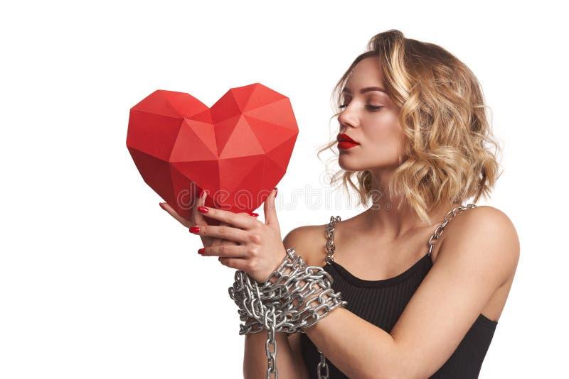 Mulher que guarda a forma de papel poligonal vermelha do coração com amarrado pelas mãos da corrente foto de stock