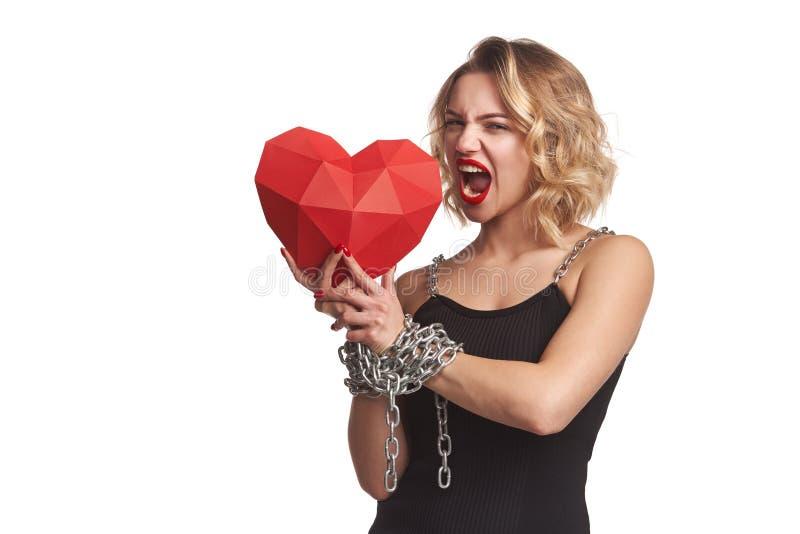 Mulher que guarda a forma de papel poligonal vermelha do coração com amarrado pelas mãos da corrente imagem de stock royalty free